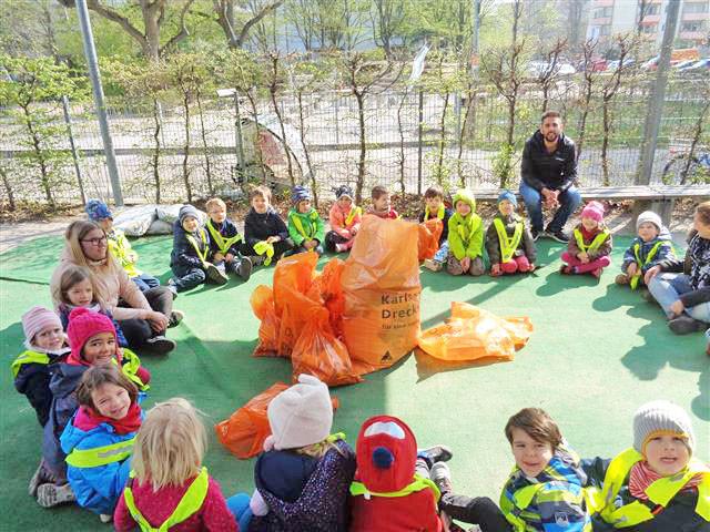 Kinder haben Müllsäcke in den Händen und sammeln Dreck ein.