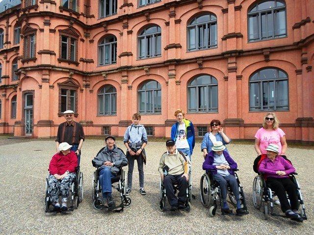 Senioren sitzen im Rollstuhl vor dem Schloss Gottesaue mit zwei jungen Männern.