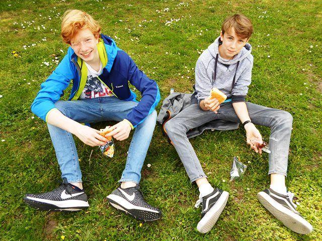 Zwei Jugendliche sitzen auf einer Wiese.