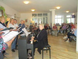 Eine Frau sitzt an einem Klavier, hinter ihr sitzen Menschen vor ihr steht ein Chor.