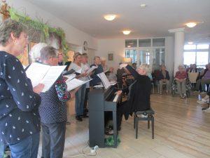Männer und Frauen stehen in Reihen und singen.