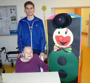 Ein junger Mann und ein Senior stehen neben einer Clownsfigur aus Pappe.