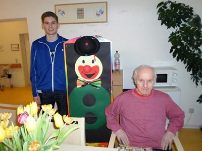 Ein junger Mann und eine Seniorin stehen neben einer Clownsfigur aus Pappe.