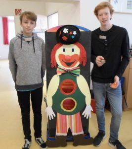 Zwei Jugendliche stehen neben einer Clownsfigur aus Pappe.
