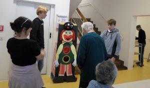 Jung und Alt stehen vor einer Clownsfigur aus Pappe.