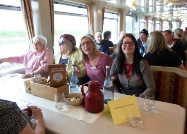 Vier Frauen sitzen auf einer Bank unter Deck auf dem Schiff und schunkeln
