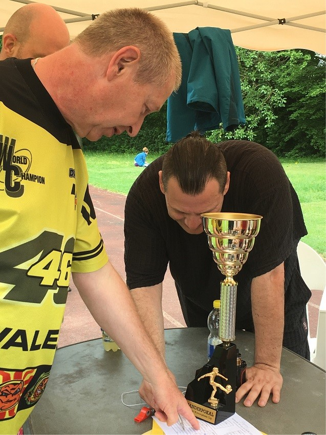 Drei Männer stehen um Pokal des Turniers und schreiben etwas