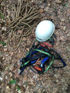 Helm mit Kletterausrüstung liegt auf dem Boden.
