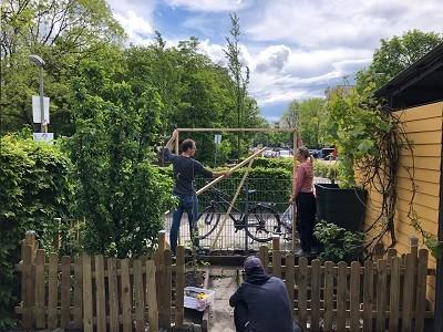 Ein Mann und eine Frau bauen ein Gerüst aus Holz im Garten der Kita auf