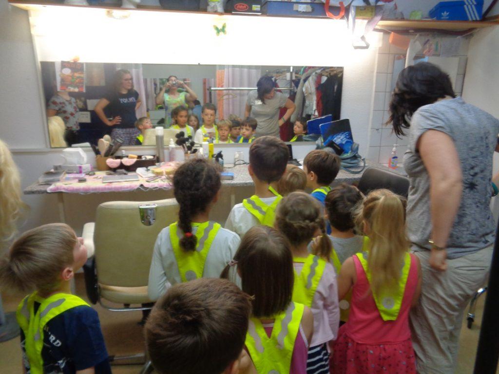 Kinder und Erzieherinnen stehen in der Garderobe der Insel und betrachten die Schminke und die beleuchteten Garderobenspiegel