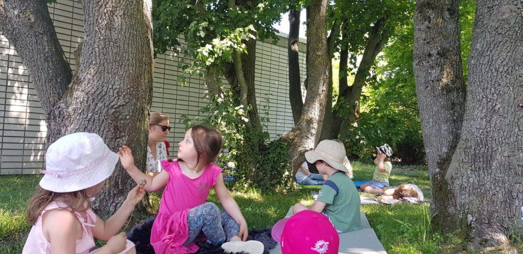 Kinder sitzen im Schatten der Bäume