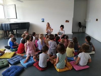 Gruppe von Kindern schauen auf zwei Frauen die eine Geschichte vorlesen und dabei Handpuppen benutzen