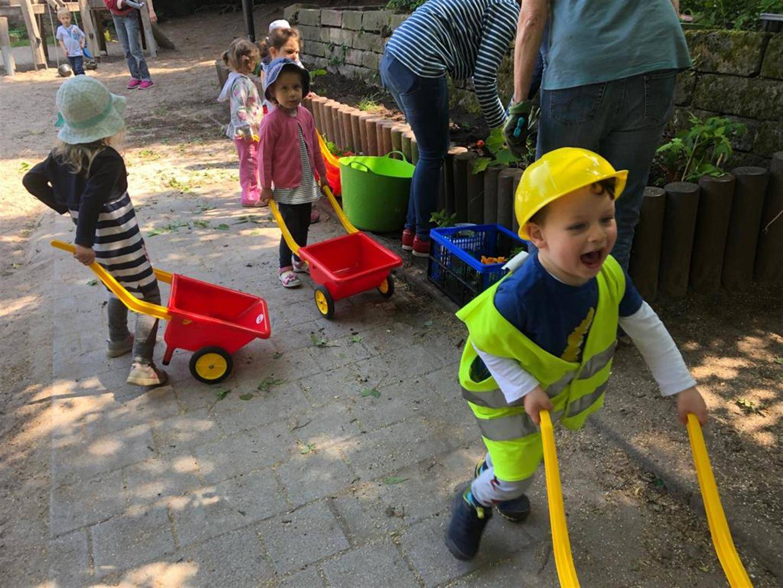 Kinder mit Schubkarren auf dem Gelände der Kita und Eltern die am Bepflanzen der Beete sind
