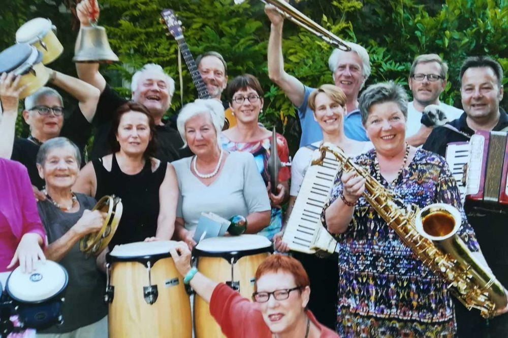 Gruppenfoto von Menschen mit Instrumenten.