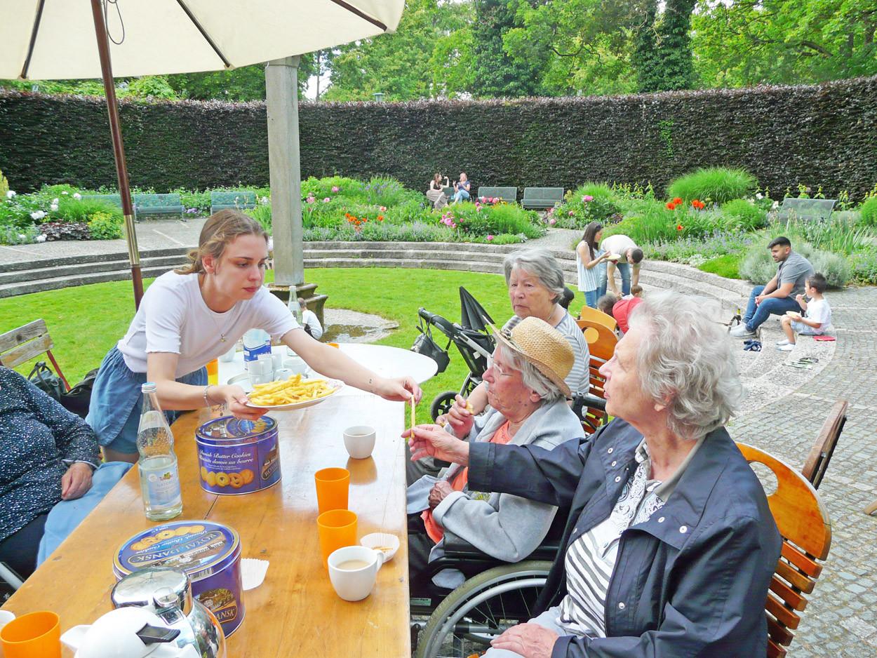Senior*innen sitzen an einem Tisch im Zoo und essen Pommes.