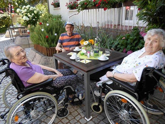 Drei Seniorinnen sitzen gemeinsam an einem Tisch und schauen fröhlich in die Kamera