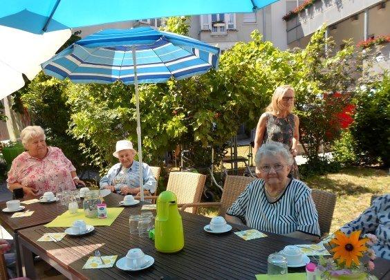Seniorinnen sitzen gemeinsam an einem Tisch bei Kaffee und Kuchen