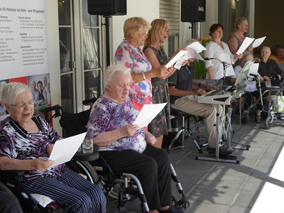Gruppe von Seniorinnen singen gemeinsam und werden von Keyboard belgeitet