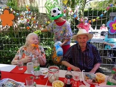 Zwei Senriorinnen und ein Clown sitzen im bunt dekoriereten Garten des Seniorenzentrums Stephanienstift