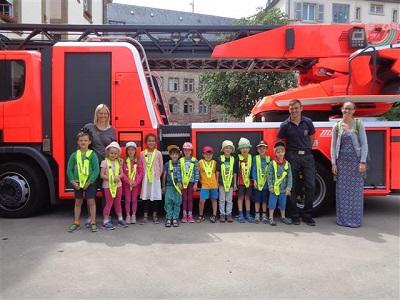 Vorschulkinder und Erzieherinnen stehen mit Feuerwehrmann vor Feuerwehrauto