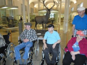 Zwei Männer und eine Frau im Rollstuhl sitzen in der Eingagnshalle des Naturkundemuseums.