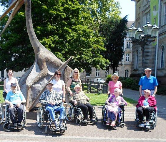 Eine Gruppe von Menschen mit und ohne Behinderung posieren vor dem Dinosaurier am Naturkundemuseum in Karlsruhe.