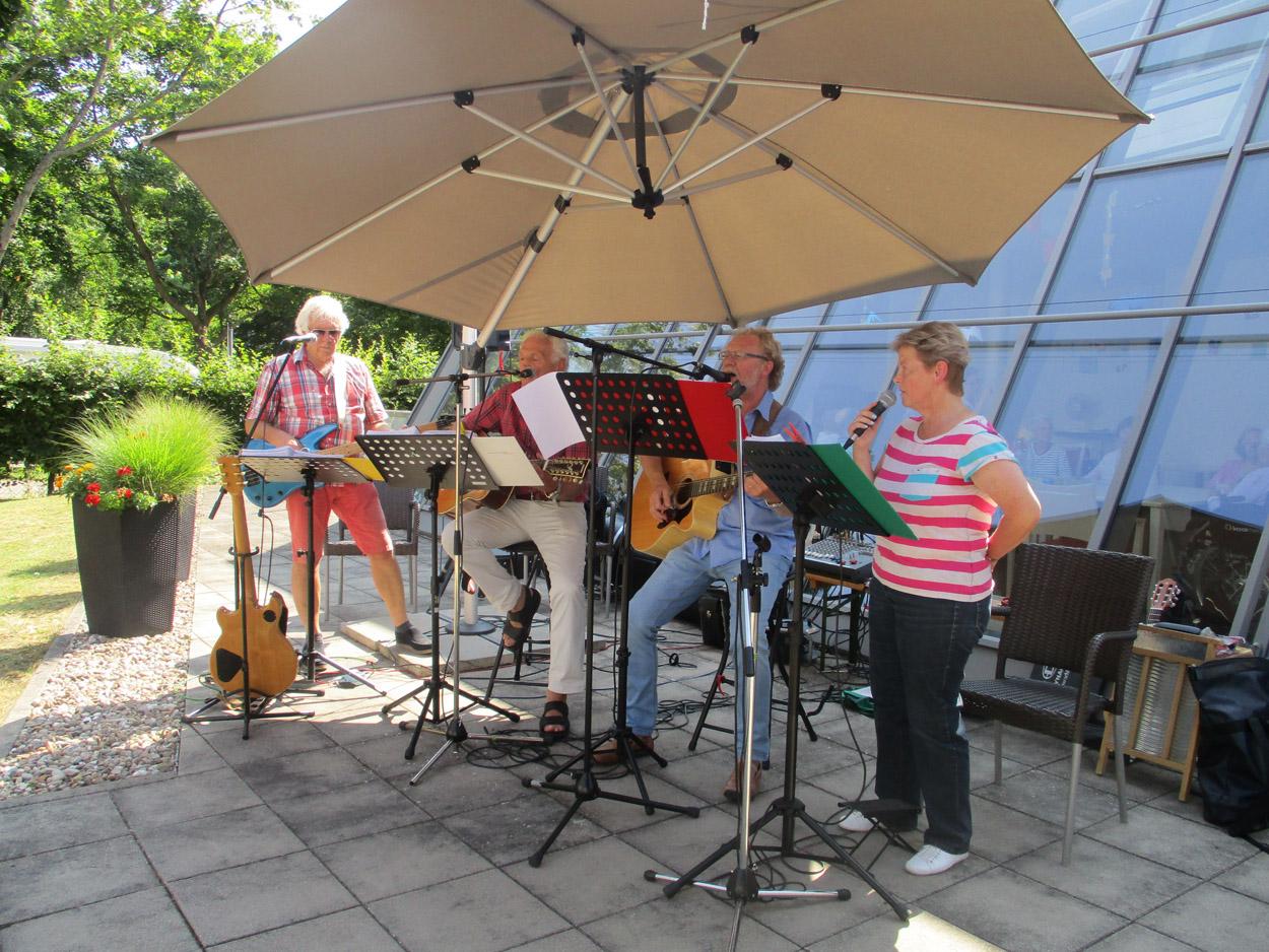 Ein Musikband tritt unter einem Sonnenschirm auf.
