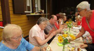 Bewohnerinnen sitzen gemeinsam am Tisch und Essen Kuchen