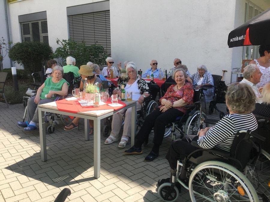 Seniorinnen sitzen beim Sommerfest zusammen.