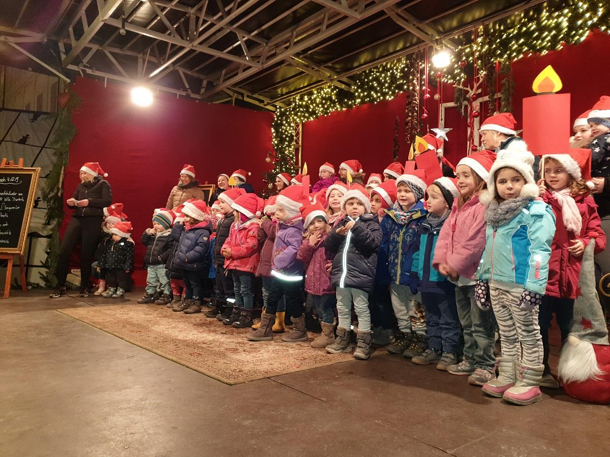 Kinder singen auf einem Weihnachtsmarkt