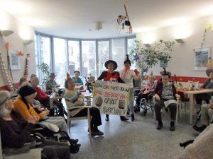 Menschen sitzen in einem Raum und feiern Fasching.