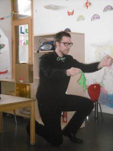Ein Mann kniet auf dem Boden und führt einen Zaubertrick vor.