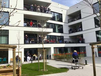 Rund 50 Menschen stehen auf ihren Balkonen in einem Seniorenzentrum und singen.