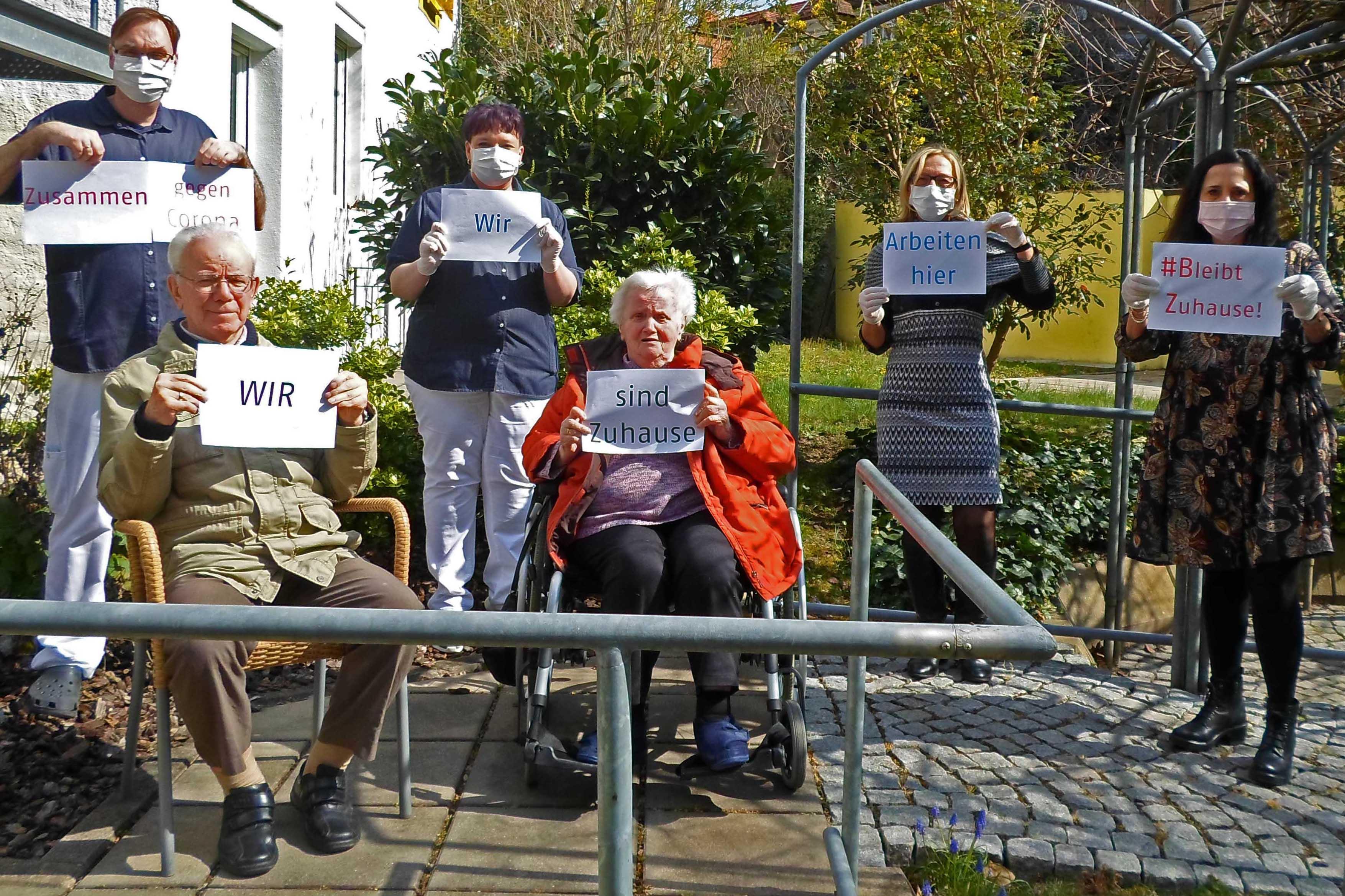 Mitarbeiter vom Seniorenheim halten Schilder in die Kamera und tragen Mundschütze.