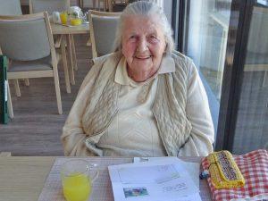 Eine Seniorin sitzt an einem Tisch und lächelt in die Kamera.
