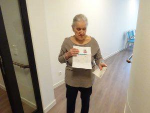Eine Seniorin hält ein gemaltes Bild in die Kamera.