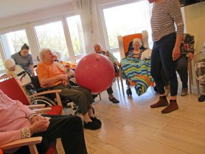 Senioren sitzen im Kreis und spielen mit einem Ball
