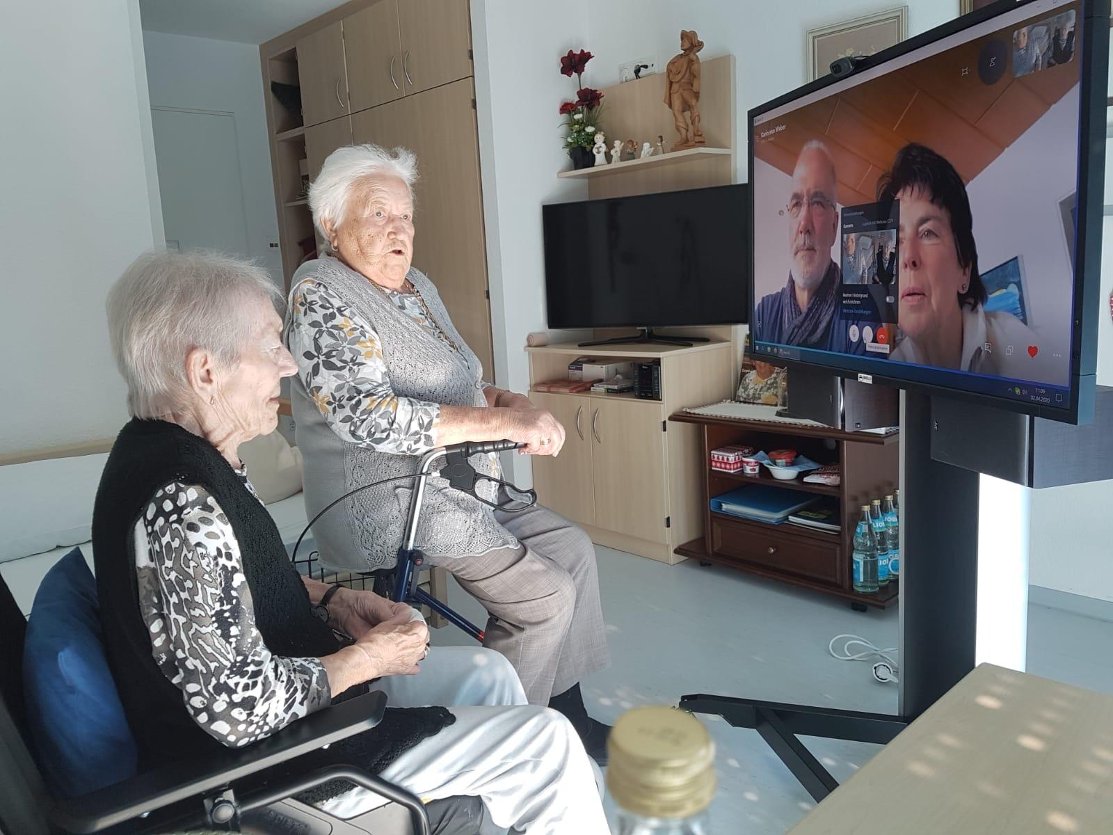 Zwei Seniorinnen sitzen vor einem Bildschirm und skypen.