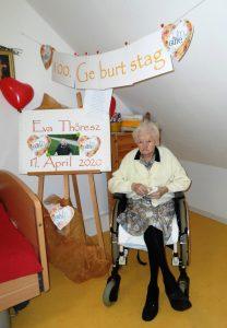 Eine Seniorin sitzt im Rollstuhl und feiert ihren 100. Geburtstag