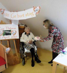 Eine Altenpflegerin überreicht einer Seniorin, die im Rollstuhl sitzt, eine Torte zu Ihrem 100. Geburtstag.