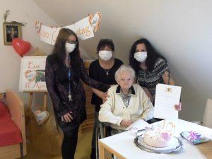 Drei Frauen gratulieren einer Seniorin zum 100. Geburtstag.