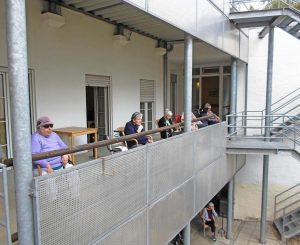 Senior*innen sitzen auf den Balkonen.