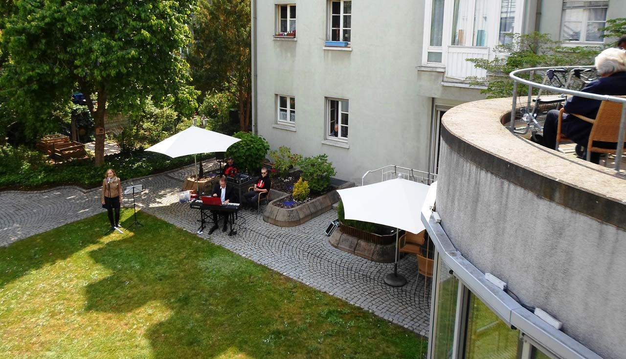 Zwei Menschen stehen im Garten und schauen nach oben zu einem Balkon.