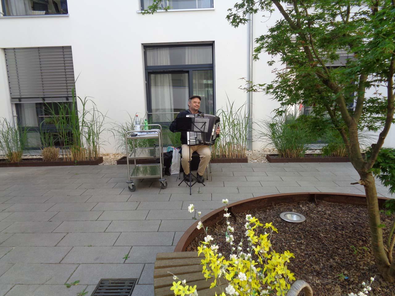 Ein Mann sitzt in einem Hof und spielt auf einer Zieharmonika.