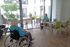 Seniorinnen sitzen in Rollstühlen in einem Haus und schauen in einen Innehofe.