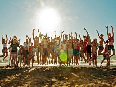 Jugendwerk AWO Karlsruhe, viele Jugendliche am Strand und springen hoch