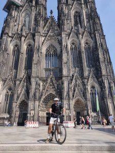 Ein Manns steht mit seinem Fahrrad vor dem Köln.