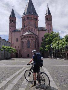 Ein Mann sitzt auf einem Fahrrad und steht vor dem Mainzer Dom.