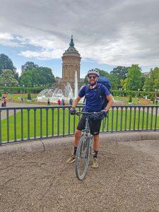 Ein Mann sitzt auf seinem Fahrrad und steht in einem grünen Park.