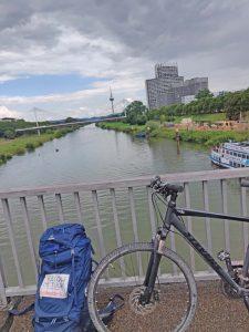 Ein Fahrrad steht vor einem Gländer an eine Brücke über einem Fluß.